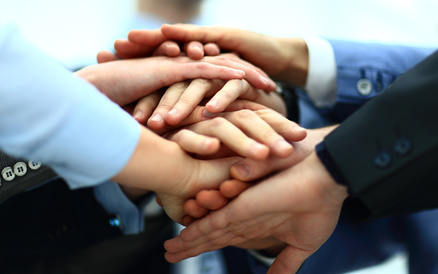 Close-up of business partners making pile of hands at meeting